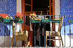 Balcony in Sintra, Portugal with blue tiles, red flowers, and tables.