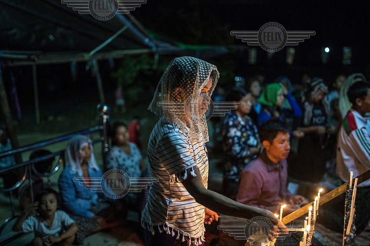 A Kachin woman prays at an IDP camp for ethnic people displaced by fighting between the Kachin Independence Army and the Myanmar military as each side seeks control of the region's jade mines.