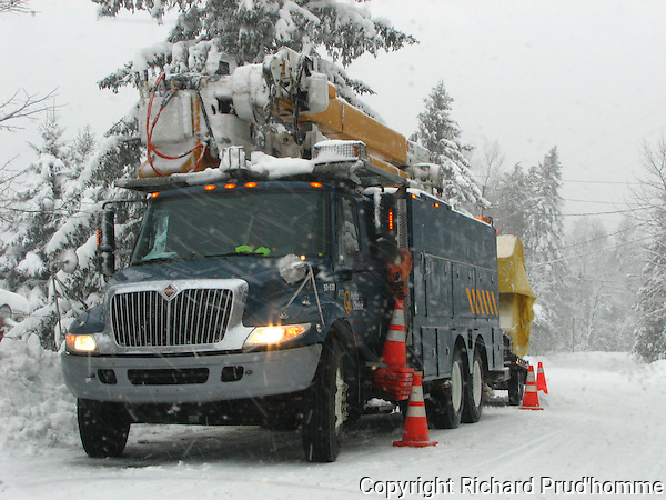 Hydro-Quebec truck parked along road in Rawdon, Quebec, repairing broken electric wires during a snowstorm
