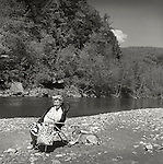 1973. Senior woman and dog relaxing along Loyalsock Creek, PA.