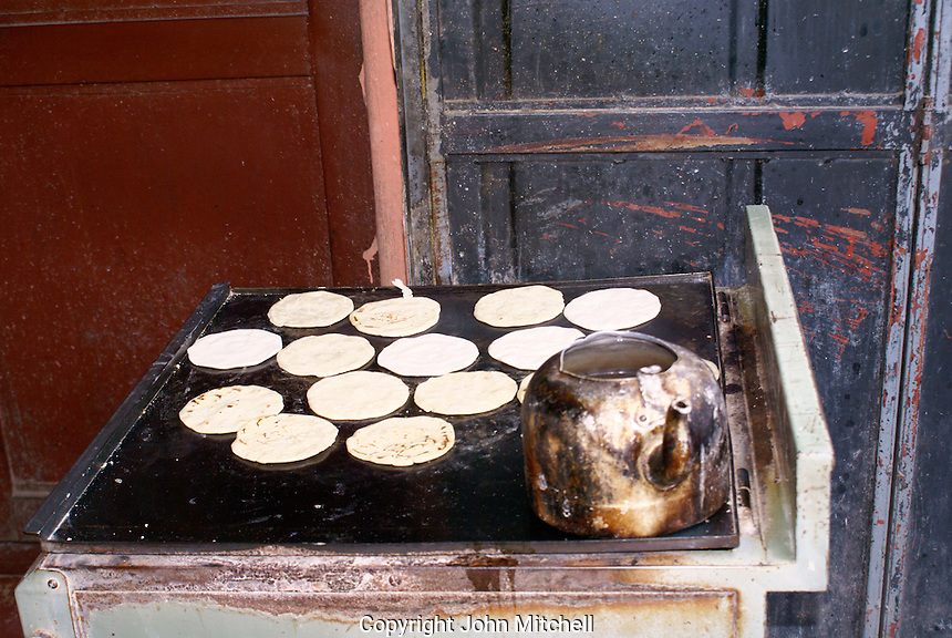 corn tortillas cooking on a grill in Coban, Alta Verapaz, Guatemala..