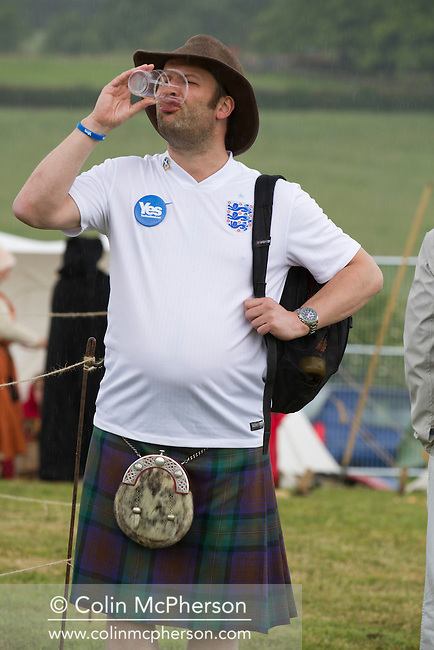 A man in a Scottish kilt, wearing an England football shirt and drinking a beer during events at Bannockburn Live, at Bannockburn, Stirlingshire. The re-enactment marked the 700th anniversary of the Battle of Bannockburn, where the Scots army under Robert the Bruce defeated the English army of Edward II. The event was part of Scotland's Year of Homecoming celebrations and was attended by a sell-out 10,000 crowd.