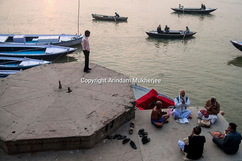 Indian men reads holy book at a ghat in Varanasi, Uttar Pradesh, India.
