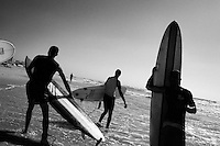 A group of surfers walk along the shore of the main beach in Gaza City as the swell rolls in from the Mediterranean Sea.