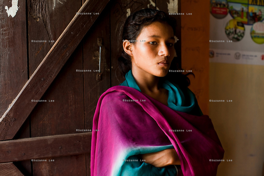 Pramila Bhujel, 13, stands at the door of the information center near her home in Lekhapharsa vilage, Surkhet district, Western Nepal, on 30th June 2012. Pramila's maternal uncle regularly abuses her so earlier this year, a fellow villager secretly married Pramila off to a man in his mid-20s but the marriage was annulled the day after when her uncle found out and wrestled her back. Now, Pramila is still mistreated by her uncle and is considered a divorcee since she spent one night with the man she was married to, but she is back in school and has ambitions to become a nurse. In Surkhet, StC partners with Safer Society, a local NGO which advocates for child rights and against child marriage. Photo by Suzanne Lee for Save The Children UK