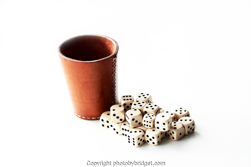 a leather cup and white dices on a white backdrop. Photographed in natural light
