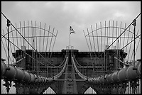 "I loved my visit to New York City, and walking across the Brooklyn Bridge was a highlight.  A strong wind was blowing, and the old brick, wood, and steel just cried out for photography.  This image focuses on the symmetry of cables and towers, with an American Flag blowing right at the viewer from the top of the tower.  I processed this in black and white to emphasize the dark, gritty feel of the old bridge.  The ""1875"" date marker is easily visible in the image.  NOTE: This image has a black border embedded into it for web display; please contact me if you're interested in ordering this image so I can print it without a black border."