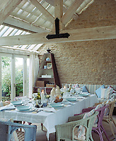 In the summer the garden room becomes the dining room, where there is a large table surrounded by pastel-coloured wicker armchairs