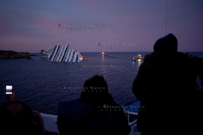 Island of Giglio, Italy, January 21, 2012.  Passenger of a ferryboat look at the stricken cruise liner Costa Concordia off the Tuscan island of Giglio..