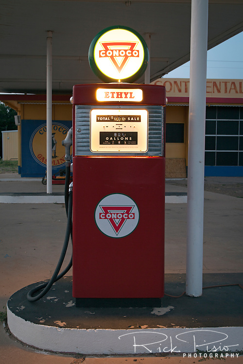 Vintage Conoco gas pump illuminated at dusk along Route 66 in Tucamcari, New Mexico.