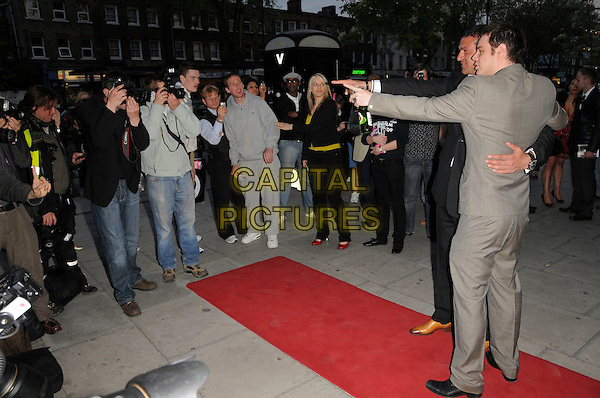 "TAMER HASSAN & DANNY DYER.The ""City Rats"" East End Film Festival VIP Screening, Genesis Cinema, Mile End Road, London, England..April 24th 2009.full length black suit grey gray hand pointing arms outstretched stella artois beer drink beverage profile photographers press .CAP/CAS.©Bob Cass/Capital Pictures."