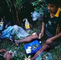 Rene Arandia Vargas, smokes a cigarette and chews on coca leaves after a hour and half hike into the Chaparé jungle to find his coca farm in Bolivia. Vargas prepares to work for eight hours, and says that the work would be impossible without the help and energy he recieves from chewing the coca leaf.