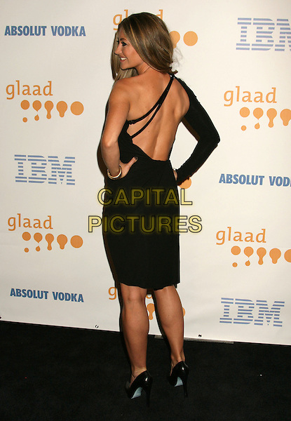 REBECCA GAYHART.20th Annual GLAAD Media Awards held at the Nokia Theatre, Los Angeles, California, USA..April 18th, 2009.full length black one shoulder dress sleeve hands on hips backless profile straps back behind rear looking over shoulder .CAP/ADM/MJ.©Michael Jade/AdMedia/Capital Pictures.