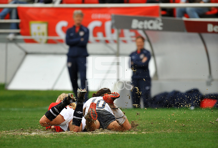 Carli Lloyd tackles an unidentified Norwegian player  through the heavy mud.  The USA defeated Norway 2-1 at Olhao Stadium on February 26, 2010 at the Algarve Cup.