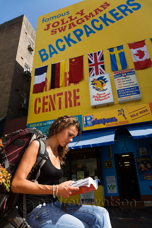 A young woman sits outside a backpacker hostel.  Kings Cross, Sydney, New South Wales, AUSTRALIA.