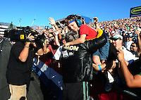Nov 14, 2010; Pomona, CA, USA; NHRA funny car driver John Force celebrates with fans after clinching the 2010 funny car championship during the Auto Club Finals at Auto Club Raceway at Pomona. Mandatory Credit: Mark J. Rebilas-