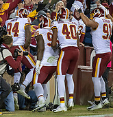 Washington Redskins linebacker Preston Smith (94) jumps into the stands as he celebrates his fourth quarter touchdown on a fumble recovery with teammates defensive tackle Da'Ron Payne (95), linebacker Josh Harvey-Clemons (40), and linebacker Ryan Kerrigan (91) against the Dallas Cowboys at FedEx Field in Landover, Maryland on Sunday, October 21, 2018.  The Redskins won the game 20 - 17.<br /> Credit: Ron Sachs / CNP