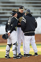 Wake Forest Demon Deacons starting pitcher John McLeod (17) and catcher Ben Breazeale (9) listen to pitching coach Dennis Healy (right) during the game against the Georgetown Hoyas at Wake Forest Baseball Park on February 16, 2014 in Winston-Salem, North Carolina.  The Demon Deacons defeated the Hoyas 3-2.  (Brian Westerholt/Four Seam Images)