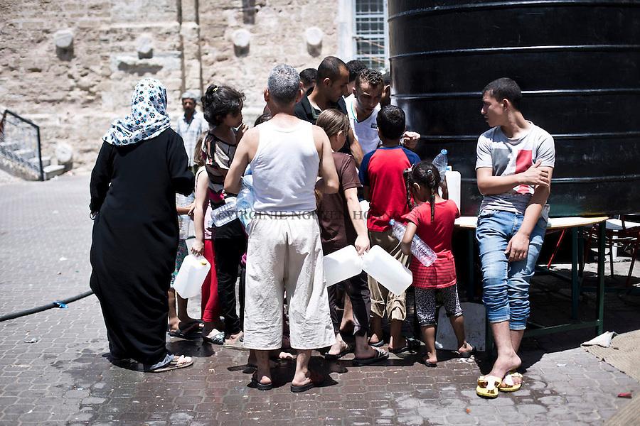GAZA: Refugees are taking water from a tank in the courtyard of the church. Few hours after, the tank was empty.30th July 2014.<br /> <br /> GAZA: des r&eacute;fugi&eacute;s prennent de l'eau d'un r&eacute;servoir dans la cour de l'&eacute;glise. Quelques heures plus tard, le tank &eacute;tait vide. 30th Juillet 2014.