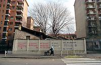 Milano, quartiere Navigli. Una donna musulmana con passeggino passa davanti a un muro con delle scritte politiche --- Milan, Navigli district. A muslim woman with stroller passes by a wall with political writings on it