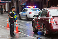 A NYPD police officer screens cars as they pass through a security checkpoint on 44th Street between 7th and 8th Avenues.