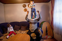 Former refugee Elvis Causevic playing with his son Aldin and watched by daughter Adna in the living room of the family home. <br /> <br /> In 1992 while volunteering at the Varazdin refugee camp Panos photographer Bjoern Steinz met and became close to Elvis, a Bosnian Muslim refugee, and his family. They shared the hardships of camp life together which Steinz documented. While the prints were archived for many years two of the images always returned to Bjoern's thoughts. 25 years later he set out to try and find out what had happened to Elvis and his family in the intervening years. Modern social media made the task surprisingly easy and they were reunited in Hadzici where Elvis now lives with his family.