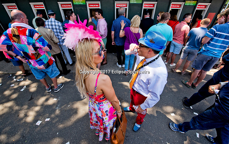ELMONT, NY - JUNE 10: A man and woman drink beer while they stand in line at the betting windows on Belmont Stakes Day at Belmont Park on June 10, 2017 in Elmont, New York (Photo by Scott Serio/Eclipse Sportswire/Getty Images)