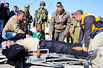 Israeli soldiers stand guard as Jewish settlers from the nearby Matsbe Yair settlement sing and dance Around a Palestinian protester on a Palestinian land after Israili settlers tried to occupy it and remove Palestinain farmers from the site in the West Bank village of Yatta, near Hebron, on January 02, 2011.Photo by Najeh Hashlamoun