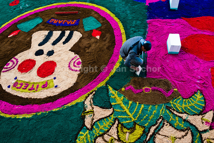 A Mexican boy creates a colorful sawdust carpet, displaying skull (Calavera), during the Day of the Dead festivities in San Juan Ixtayopan, Mexico, 1 November 2016. Skulls, skeletons and the other death symbols are used to adorn graves, altars and offerings during the Day of the Dead (Día de Muertos). A syncretic religious holiday, combining the death veneration rituals of the ancient Aztec culture with the Catholic practice, is celebrated throughout all Mexico. Based on the belief that the souls of the departed may come back to this world on that day, people gather at the gravesites in cemeteries, praying, drinking and playing music, to joyfully remember friends or family members who have died and to support their souls on the spiritual journey.