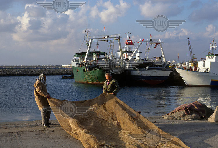 Fishermen arranging nets in the port, with fishing trawlers docked behind.