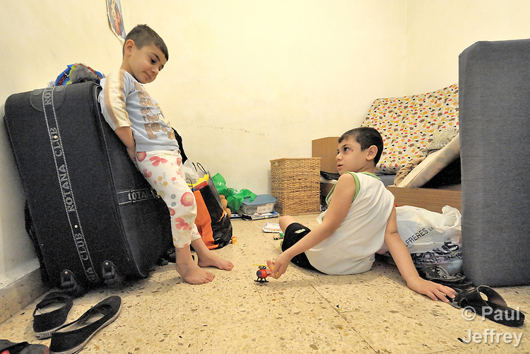 Milad Faris, age 6 (left), and his brother Stephen, age 9, play on the floor of their small apartment in Beirut. Their father was killed February 29, 2008, in Mosul, Iraq, while working as a driver and assistant to the Chaldean archbishop of Mosul, Archbishop Faraj Rahho, who was later found dead. The boys came to Lebanon in May with their mother and sister, and currently live as refugees in Beirut. Tensions run high with neighbors who reject the Iraqis, however, and Stephen was beaten by other children on October 2. The family has received assistance from the Caritas Lebanon Migrant Center, which is funded by Catholic Relief Services, the relief and development agency of the U.S. Catholic community.