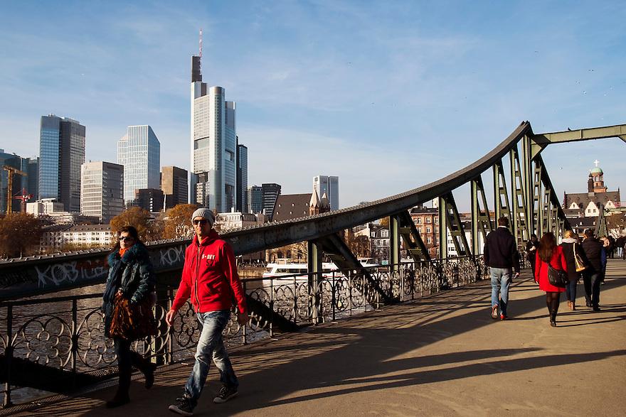Duitsland, Frankfurt am Main, 23 nov 2014<br /> Voetgangersbrug Eisernen Steges over de Main. Toeristische trekpleister omdat het een mooie brug is en uitzicht geeft over het financiele centrum van Duitsland. Toeristen maken er selfies, er wordt muziek gemaakt en er hangen duizenden liefdeslotjes aan de brug.<br /> Frankfurt  is het voornaamste financi&euml;le centrum van Duitsland: de Deutsche Bundesbank en de Duitse beurs zijn er gevestigd evenals het hoofkantoor van de Europese Centrale Bank.<br />  <br /> Foto: (c) Michiel Wijnbergh