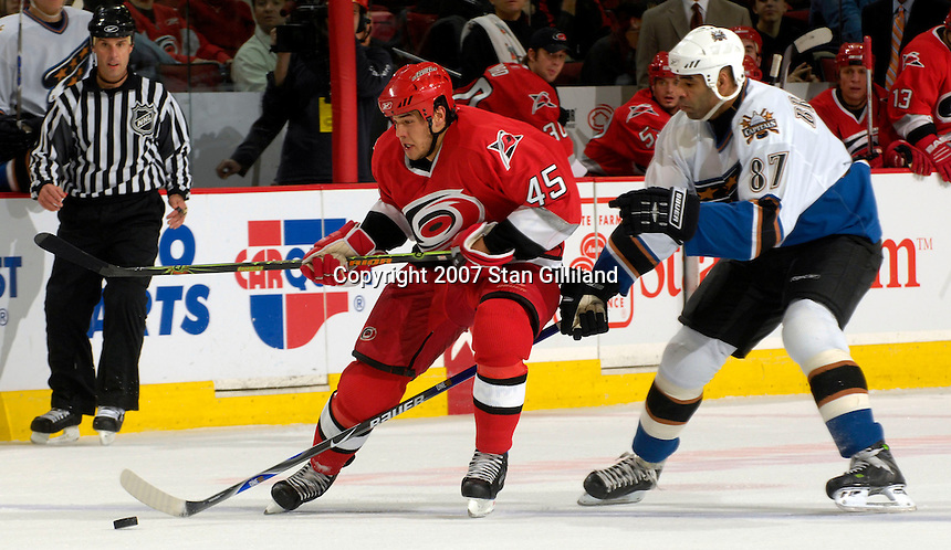 Carolina Hurricanes' David Tanabe tries to maintain control of a puck defended by the Washington Capitals' Donald Brashear Thursday, March 22, 2007 at the RBC Center in Raleigh, NC. Carolina won 4-3.