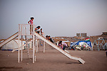 DOMIZ, IRAQ: Children play on a slide in the Domiz refugee camp..Over 7,000 Syrian Kurds have fled the violence in Syria and are living in the Domiz refugee camp in the semi-autonomous region of Iraqi Kurdistan...Photo by Ali Arkady/Metrography