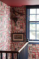 A stairwell is decorated with Lewis & Wood's Trade Cards wallpaper. The Georgian sash window is painted a vibrant blue and the red ceiling is reflected in the wallpaper background.