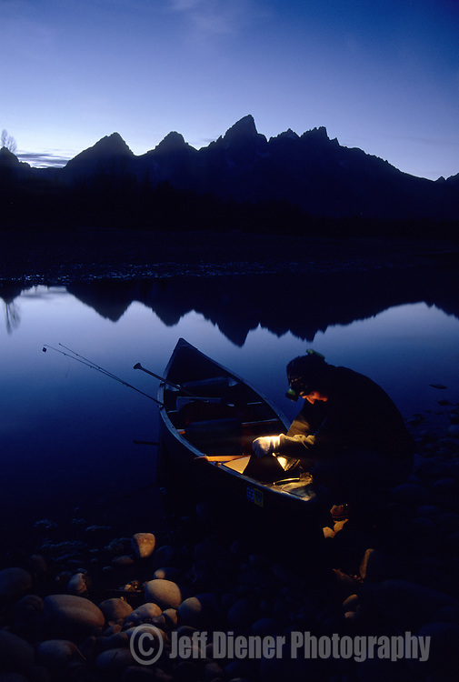 A man packs fishing gear into a canoe along the Snake River in Grand Teton National Park, Wyoming.