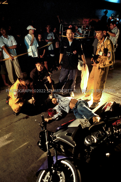 Por Tek Teung?the 'Body Snatchers'. .Bangkok, Thailand...Por Tek members point to the head of a young motorcyclists murdered on the streets of Bangkok. Besides collecting bodies and collecting evidence, Por Tek members also helps the police searching for and arresting suspects....Automobile accidents are one of tthe leading causes of death in Thailand, especially for young men. Despite this, Bangkok still lacks proper ambulance services, forcing charities like 'Por Tek Teung' to fill in the gap. Nicknamed the 'body snatchers', such groups appeal for contributions from Buddhist citizens hoping to make merit by contributing to such a worthy cause as caring for the dead...All photographs ©2003 Stuart Isett.All rights reserved.