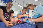 Ten-month old Johan gets an IV inserted in his hand by Nurse Jazmine Gino-Gino (right) in the emergency room of the Mary Johnston Hospital in Manila, Philippines. Holding the boy down is Nurse Brian Grape Maningding. Johan's mother, Mirakel Guarin, comforts the boy.<br /> <br /> The hospital is supported by United Methodist Women.