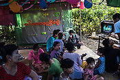 Attendees of the marriage ceremony drink tea and sing along to Karaoke in Kant Ma Lar Chang Village in Pyapon district of Myanmar.