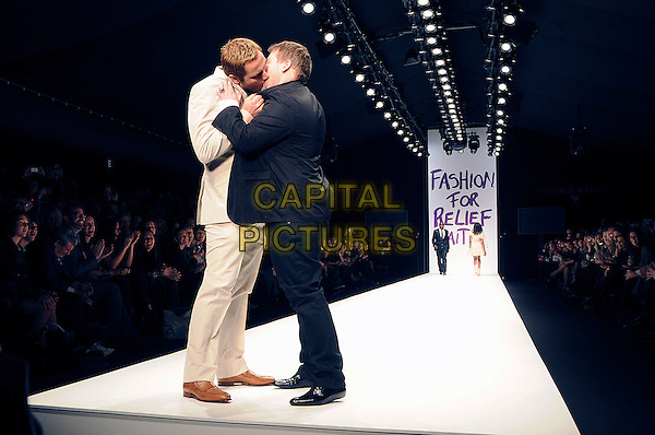 DAVID WALLIAMS & JAMES CORDEN.The Fashion For Relief Haiti 2010 show for London Fashion Week Autumn/Winter 2010 at Somerset House, London, England..February 18th, 2010.LFW catwalk runway full length black beige suit profile kiss kissing pink shirt white funny .CAP/CAS.©Bob Cass/Capital Pictures.