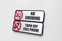 Signs prohibiting smoking and the use of cell phones at the entrance to a building in New York on Saturday, April 15, 2017.  (© Richard B. Levine)