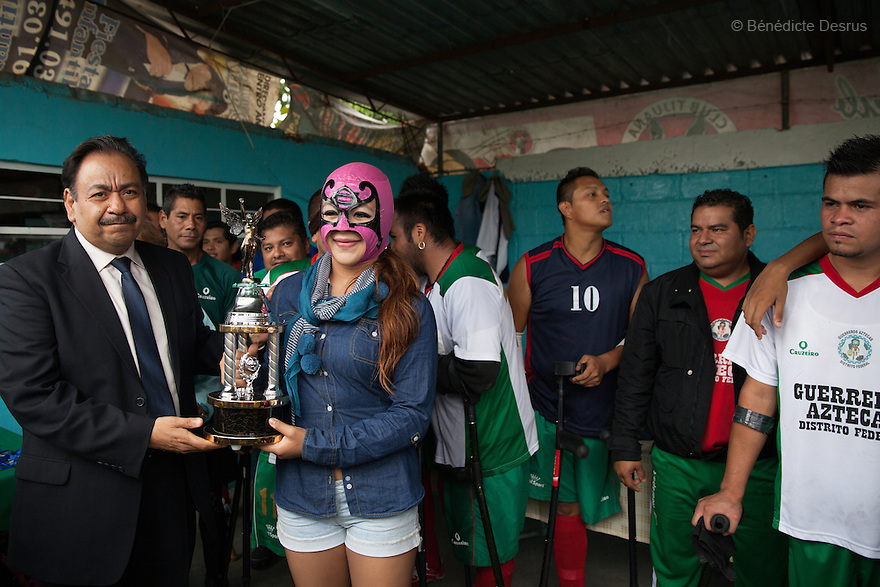 "Players from Guerreros Aztecas pose for a group photo with a ""lucha libre"" wrestler after a match in Mexico City, Mexico on July 5, 2014. Guerreros Aztecas (""Aztec Warriors"") is Mexico City's first amputee football team. Founded in July 2013 by five volunteers, they now have 23 players, seven of them have made the national team's shortlist to represent Mexico at this year's Amputee Soccer World Cup in Sinaloa this December. The team trains twice a week for weekend games with other teams. No prostheses are used, so field players missing a lower extremity can only play using crutches. Those missing an upper extremity play as goalkeepers. The teams play six per side with unlimited substitutions. Each half lasts 25 minutes. The causes of the amputations range from accidents to medical interventions – none of which have stopped the Guerreros Aztecas from continuing to play. The players' age, backgrounds and professions cover the full sweep of Mexican society, and they are united by the will to keep their heads held high in a country where discrimination against the disabled remains widespread. (Photo by Bénédicte Desrus)"