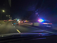 An Austin Police Department (APD) police cruiser with the lights flashing and tow truck towed a distressed car along the Mopac Loop 1 highway.