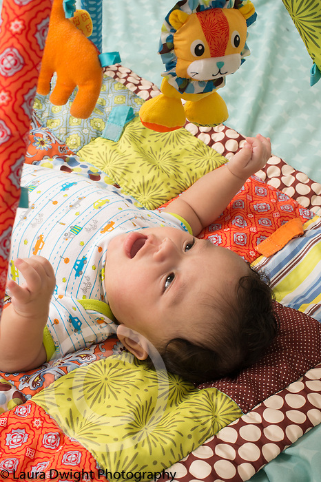 4 month old baby boy interested in hanging toys, on back