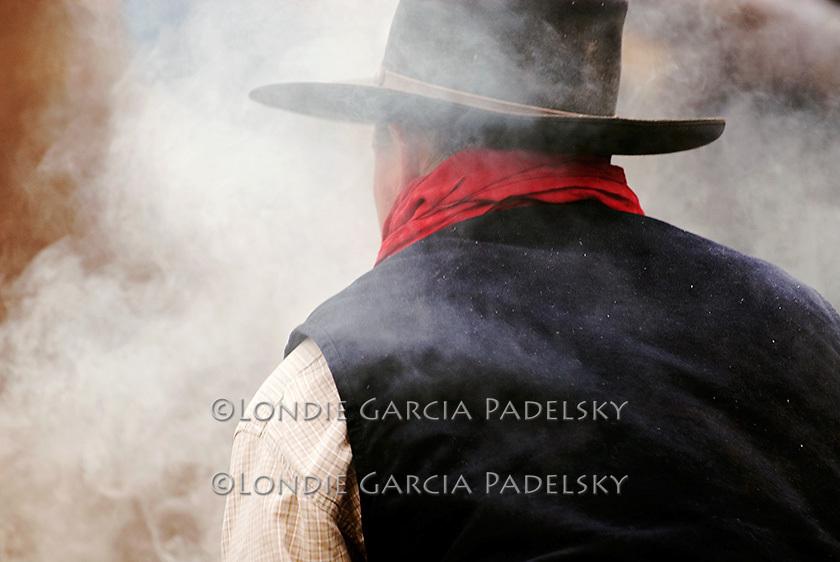 Cowboy branding cattle at a roundup in Santa Margarita, California