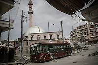 A bus used as barricade that protects from sniper fire is seen beside a mosque at Sheikh Maksoud front line, a majority-Kurdish neighborhood took by opposition fighters since weeks ago, and targeted by Syrian army aircraft bombardments and heavy shelling, forcing thousands of residents to flee into safe areas outside of Aleppo City.