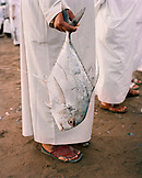 OMAN, Muscat, low section of man holding fish at market
