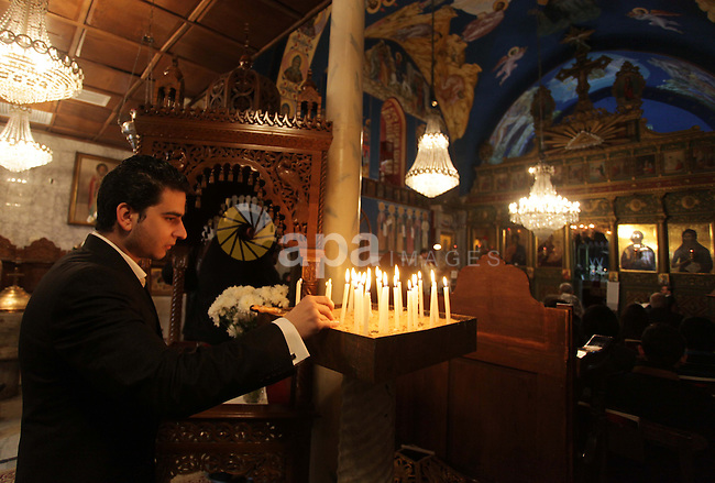A Palestinian Orthodox Christian man lights a candle in a church during Christmas celebrations on January 7, 2013 in Gaza City. The Orthodox Church celebrates Christmas and other religious holidays according to the Julian calendar, while other Christian churches have adopted the later Gregorian calendar. Photo by Ashraf Amra