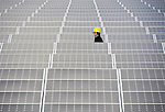 Staff walk through the rows of photovoltaic panels at the Minamisoma Agri-Solar Park in Minamisoma, Fukushima, Japan on 10 Feb 2013. More than 2,000 solar panels will power the domes, inside which farmers affected by the 2011 tsunami and nuclear accident will be able to grow produce. Excess power will be sold to a local utilities company. .Photographer: Robert Gilhooly
