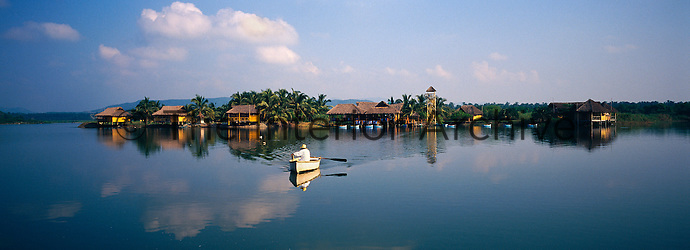 A man rows a boat across the lagoon with the traditional stilted, thatched huts of the hotel complex in the background